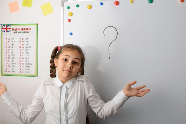 Verwirrtes schulmädchen kennt die antwort auf die frage nicht und streckt die hände zur seite