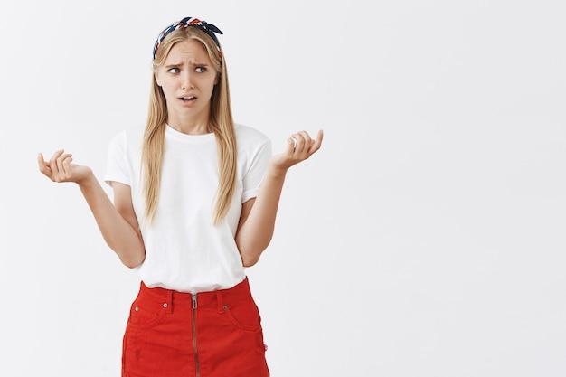 Verwirrtes und verwirrtes junges blondes mädchen, das gegen die weiße wand aufwirft