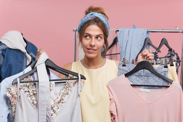 Verwirrtes weibliches model, das kleiderbügel mit kleidung in beiden händen hält und versucht, etwas passendes zu wählen. frau, die zwischen den einkäufen zögert. menschen, mode, verkauf, kleidung und einkaufskonzept