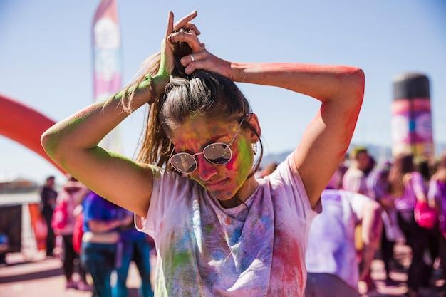 Verwirrung der jungen frau in der holi farbtragenden sonnenbrille, die draußen ihr haar bindet