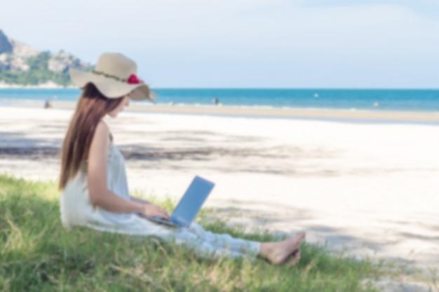 Verwischen sie bild der jungen asiatin, die laptop im kleid sitzt, das auf dem strand sitzt