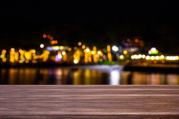 Verwischen sie caférestaurant oder -resort nahe dem meer der dunklen hölzernen tabelle mit hellem goldbokeh hintergrund
