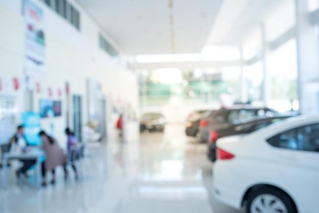 Verwischen sie den hintergrund des autos und des ausstellungsraums an verwischt an arbeitsplatz oder am abstrakten hintergrund der flachen bürotiefe des fokus.