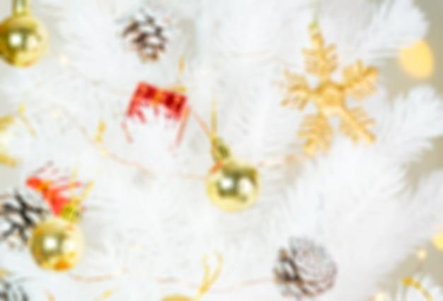 Verwischen sie hintergrund des weihnachtsdekorationsgegenstandes, der am weißen weihnachtsbaum, ferienzeit hängt.