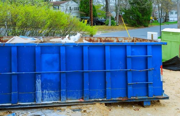 Verwischen sie müllcontainer, bereiten sie abfall und mülltonnen nahe neubau des wohnhausgebäudes auf