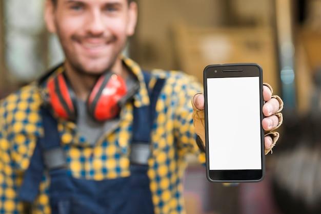 Verwischen sie porträt eines männlichen tischlers, der seinen smartphone zeigt, der weißen schirm anzeigt
