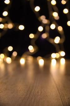 Verwischen sie weihnachtslichter auf hölzernen planken, niedrige schärfentiefe mit copyspace