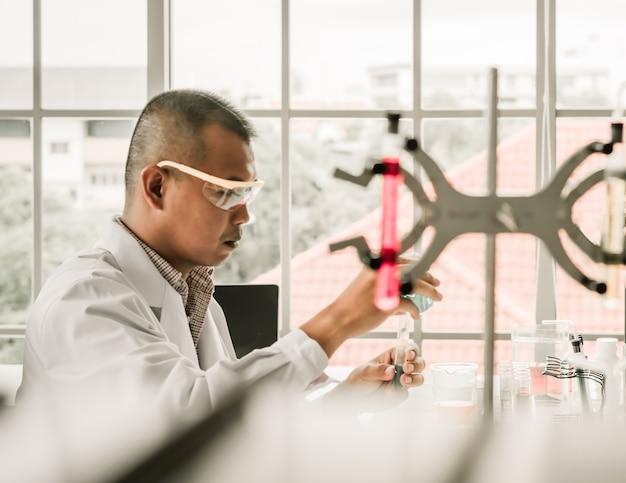 Verwischt vom asiatischen mannwissenschaftler im labor, das die flüssigkeit vom becher zu tes gießt