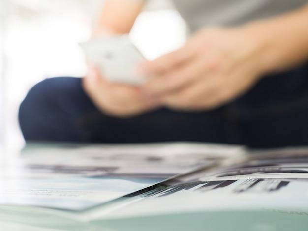 Verwischt von den männlichen händen, die mit intelligentem telefon des handys halten und arbeiten