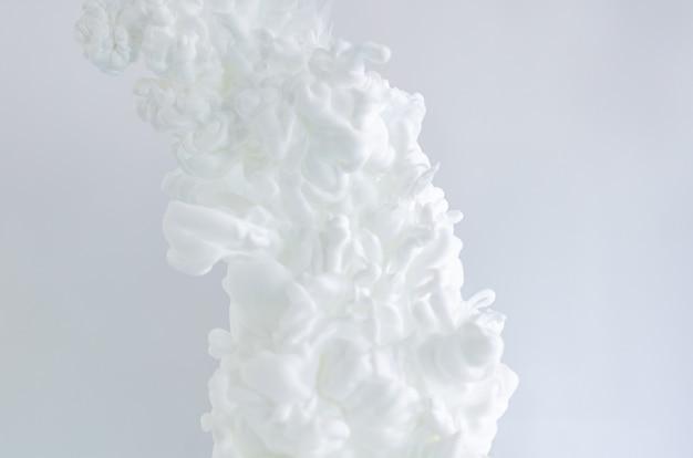 Verwischte und fokussierte weiße plakatfarbe, die sich im wasser für abstraktes und backgorundes konzept auflöst.