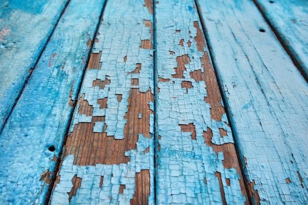 Verwitterte holzbretter mit rissiger blauer farbe