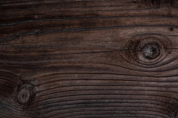 Verwitterter dunkelbrauner holzhintergrund mit beschaffenheit. textur aus braunem altem holz. breite nahaufnahme der verbrannten brettstruktur. ein holzmuster.