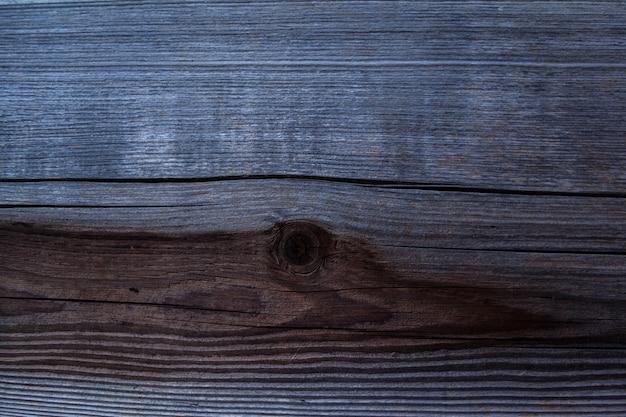 Verwitterter dunkler holzhintergrund mit beschaffenheit. textur aus braunem und grauem altholz. breite nahaufnahme der verbrannten brettstruktur. eine holzoberfläche.