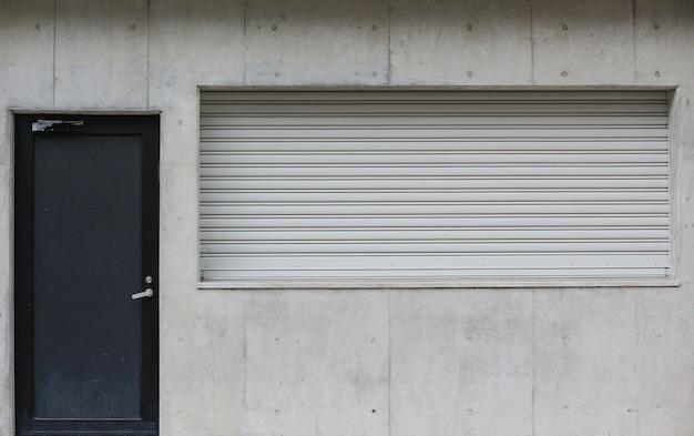 Verwittertes dunkles tür- und fensterladenfenster des metalls auf zementwandhintergrund.