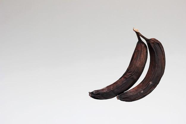 Verwöhnte alte bananen. zwei faul geschwärzte und getrocknete bananen.