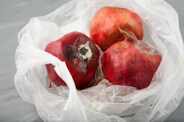Verwöhnte granatäpfel mit schimmel in einweg-plastiktüte