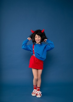 Verwöhntes kind, ungezogenes mädchen, kinderlaunen. schönes kleines mädchen in perücke mit roten koboldhörnern, die charakter zeigen. konzept der kinderkrisenpsychologie. foto in voller länge