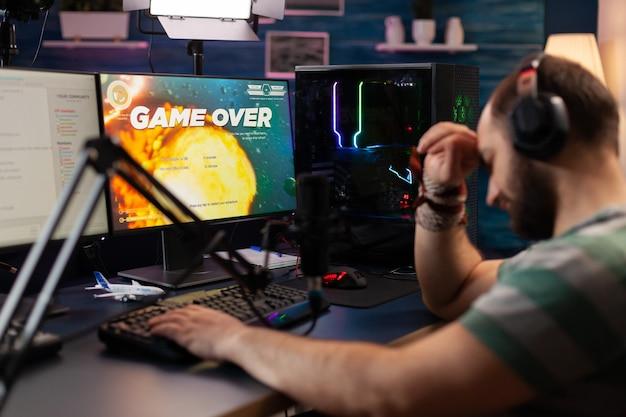 Verwüsteter streamer mit kopfhörern, der mit anderen spielern diskutiert, während er das weltraum-shooter-spiel spielt. pro gamer, der online-videospiele mit professionellem mikrofon und headset streamt