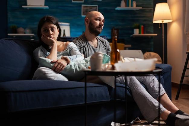 Verwundbares, verängstigtes, deprimiertes, frustriertes junges paar, das auf der couch sitzt