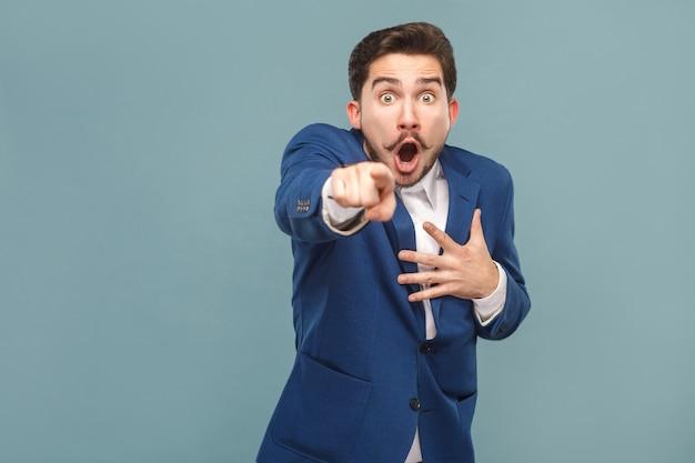 Verwunderter mann, der mit schockiertem gesicht mit dem finger auf die kamera zeigt