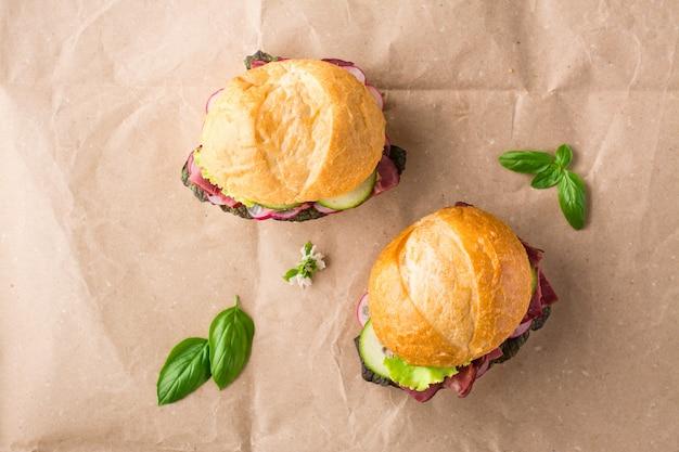 Verzehrfertige hamburger mit pastrami, gurke, rettich und kräutern auf kraftpapier. amerikanisches fastfood. ansicht von oben