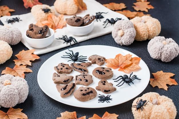 Verzehrfertiger halloween-genuss - lebkuchen mit schokoladenglasur auf einem teller auf dem tisch mit kürbissen. traditionelle feier.
