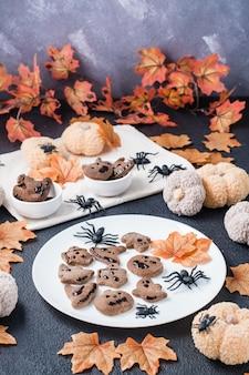 Verzehrfertiger halloween-genuss - lebkuchen mit schokoladenglasur auf einem teller auf dem tisch mit kürbissen und blättern. traditionelle feier. vertikale ansicht