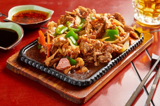 Verzehrfertiges chinesisches essen, serviert mit saucen und stäbchen