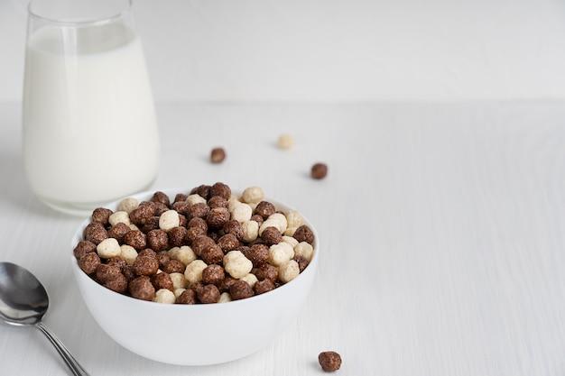 Verzehrfertiges gesundes müsli in einer schüssel, serviert mit löffel und glas milch zum frühstück auf dem tisch