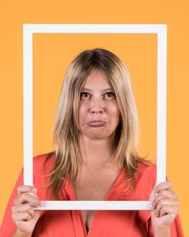 Verziehende lippen der frau beim halten der weißen grenzbilderrahmenfront ihres gesichtes
