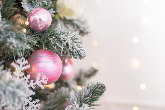 Verziert in einem rosa weihnachtsbaum auf einem unscharfen, funkelnden und fabelhaften hintergrund.