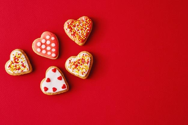 Verziert mit zuckerglasur und glasierten herzformplätzchen auf roter oberfläche mit kopienraum. valentinstag-food-konzept