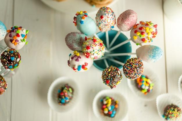 Verzierte bonbons und cake pops auf holzbrettern