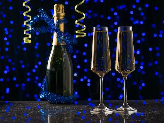 Verzierte champagnerflasche und zwei gefüllte gläser auf blauen bokeh-lichtern. ein beliebtes alkoholisches getränk.