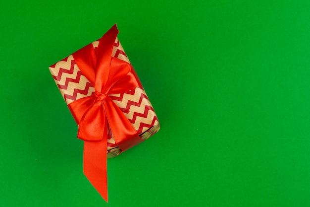 Verzierte geschenkbox auf einer draufsicht der grünen, flachen lage