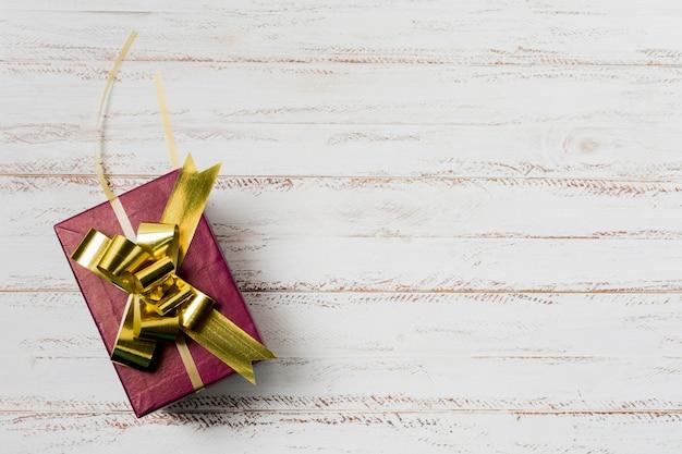 Verzierte geschenkbox mit goldenem band auf strukturierter weißer holzoberfläche
