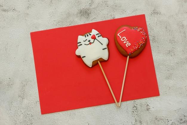 Verzierte herzformplätzchen auf rotem blatt für ihren text. lebkuchen in form einer katze und eines herzens. platz für text. konzept valentinstag. karte