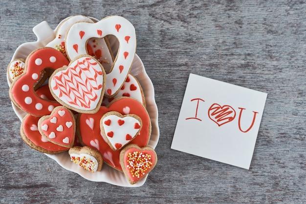 Verzierte herzformplätzchen und papierblatt mit aufschrift ich liebe dich auf einem grau auf grauer oberfläche. valentinstag-konzept