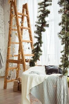 Verzierte holztreppe und hängematte mit tannenzweigen für weihnachtsferien