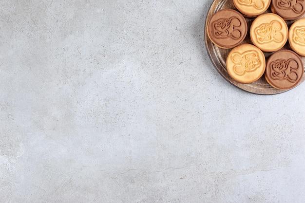 Verzierte kekse auf holzbrett im marmorhintergrund. hochwertiges foto