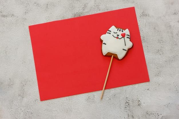 Verzierte kekse auf rotem blatt für ihren text. lebkuchenplätzchen in form einer katze. platz für text. konzept valentinstag. karte