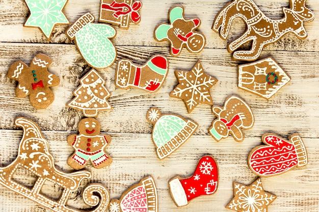 Verzierte lebkuchenplätzchen auf einem weißen hölzernen hintergrund. weihnachtsmuster.