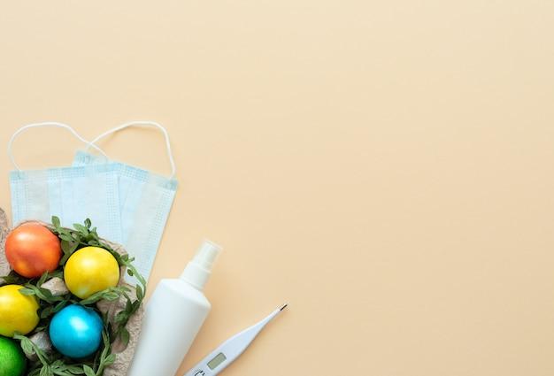Verzierte ostereier liegen im karton auf gelb mit medizinischer gesichtsmaske, thermometer und desinfektionsmittel