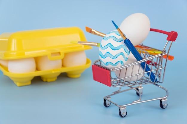 Verzierte ostereier und pinsel im einkaufswagen mit gelber eierablage gefüllt mit eiern auf blauem hintergrund.