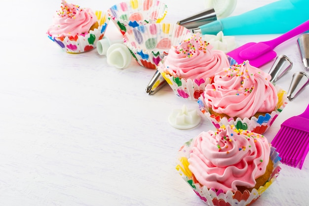 Verzierte rosa geburtstagskleine kuchen und -kochgeschirr