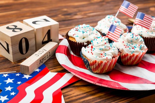 Verzierte schlagsahnekleine kuchen mit amerikanischen flaggen auf platte und symbolen der unabhängigkeit
