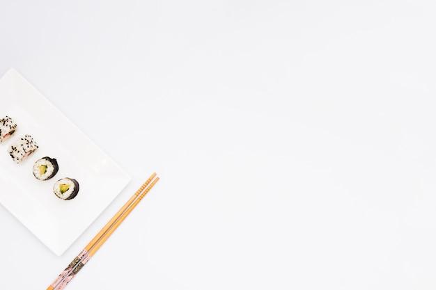 Verzierte sushirollen auf platte und essstäbchen über weißem hintergrund mit raum für text