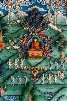 Verzierte wand, die über buddha-geschichte in der bhutanischen kunst innerhalb des königlichen bhutanischen klosters in bodh gaya, bihar, indien erklären.