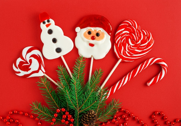 Verzierte weihnachtsbonbons auf rotem hintergrund