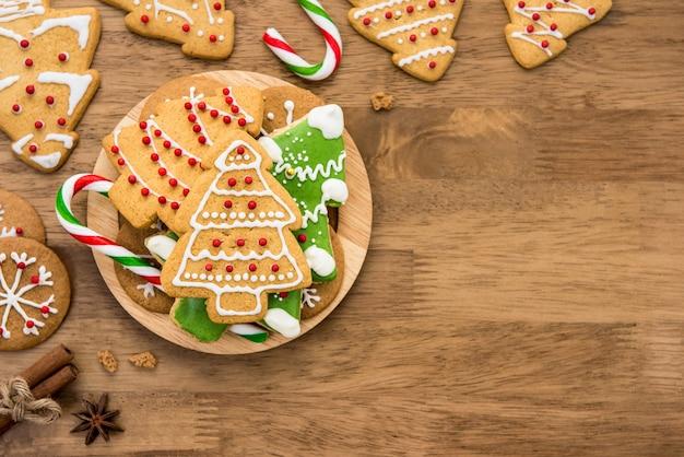 Verzierte weihnachtslebkuchenplätzchen auf hölzernem hintergrund
